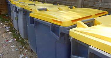 A row of bins with yellow lids