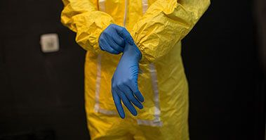A worker in a hazmat suit putting on some gloves