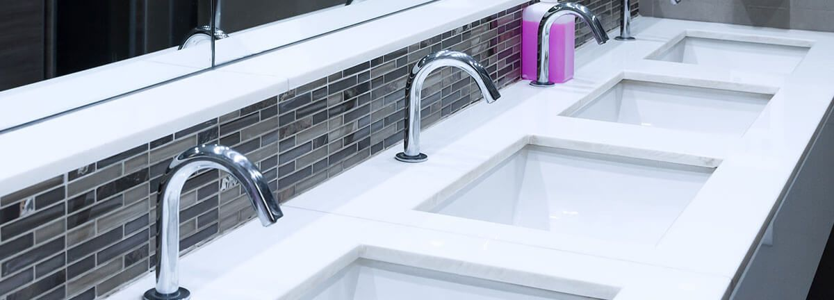 A row of sinks with some pink soap