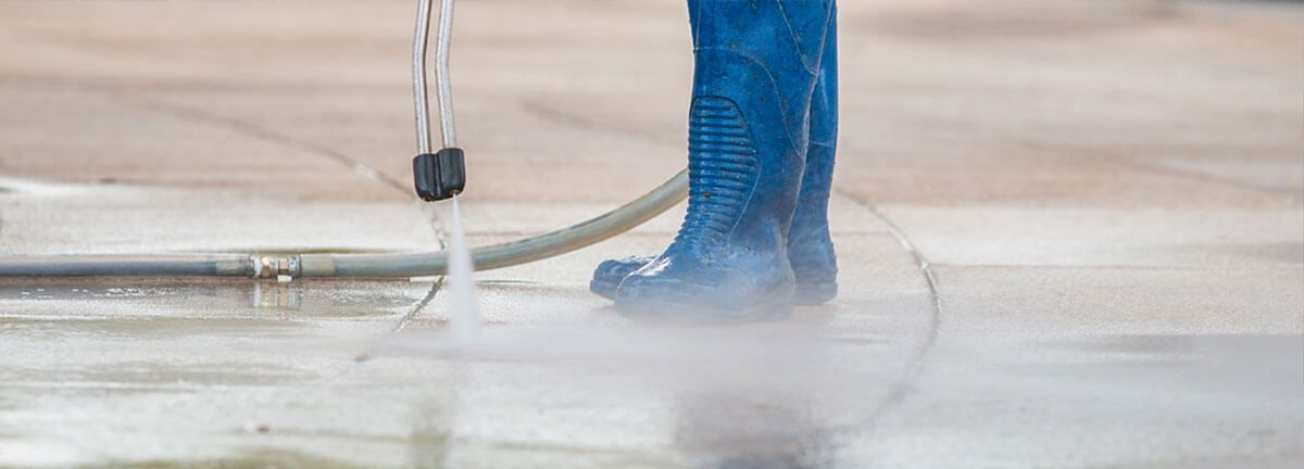 A worker power washing the floor